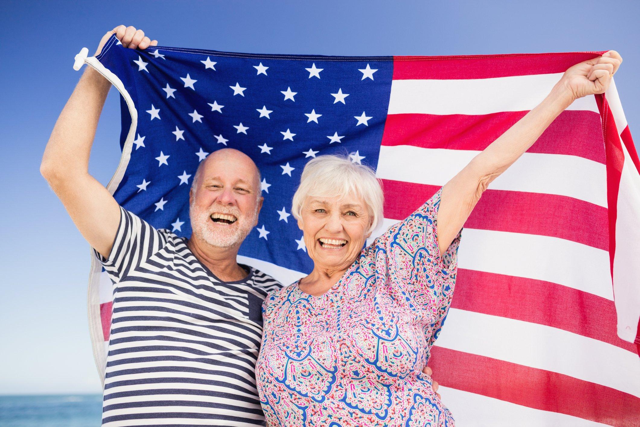 Senior couple holding american flag